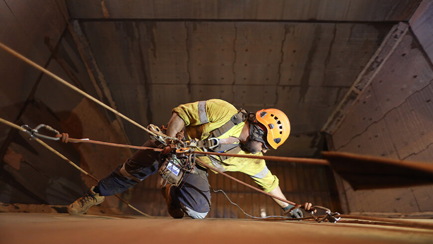 View from above of a worker using rope access to work